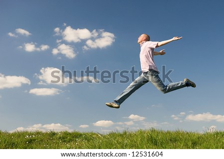 Young man is jumping over a green. Use it for lifestyle concepts - stock photo