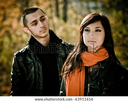 Young man is looking at beauty girl in fall outdoor