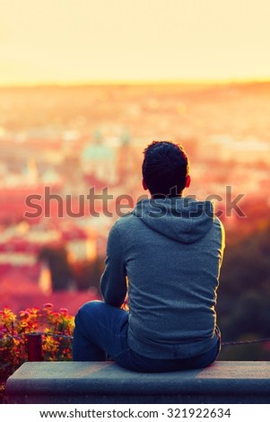 Young man is looking at the sunrise. - stock photo