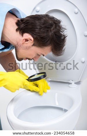 Young man is looking through magnifying glass in a toilet.