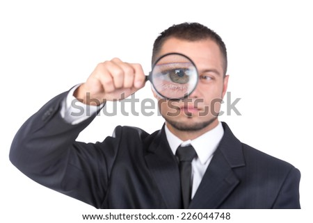Young man is looking through the magnifying glass, over white background.