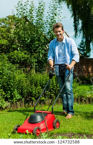 Young man is mowing the lawn in summer with a mowing machine - stock photo