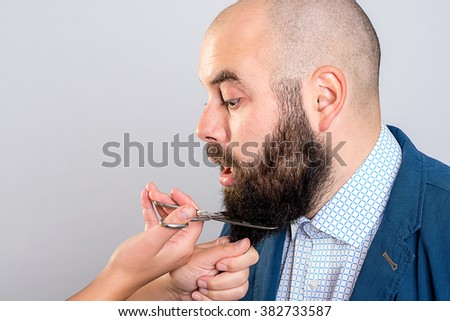 young man is not so happy with beard- cutting