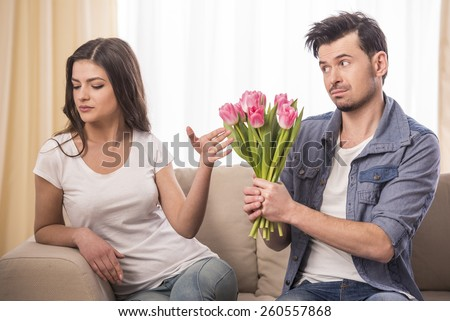 Young man is offering a bunch of flowers to his angry girlfriend at home. - stock photo