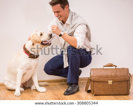 Young man is playing with a dog. - stock photo