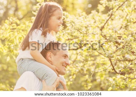 young man is playing with his daughter in the nature. The father is standing and carrying girl on his back. He is stretching arms sideways. Happy family playing in nature