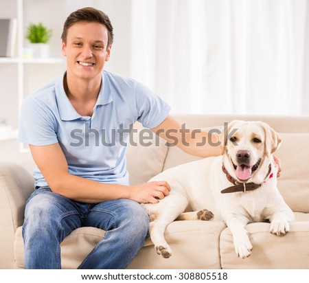 Young man is playing with his dog at home. - stock photo