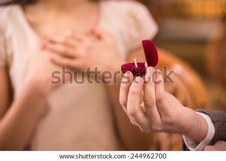 Young man is presenting engagement ring to his girlfriend. - stock photo