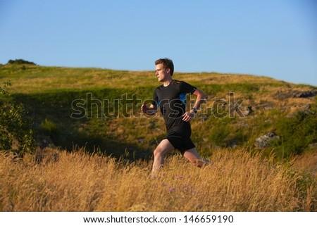 Young man is running in nature - selective focus  - stock photo