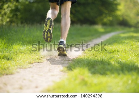Young man is running in sunny nature - stock photo