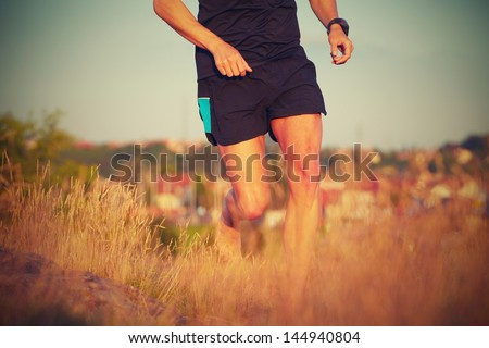 Young man is running on summer meadow - lovely sunset light - stock photo