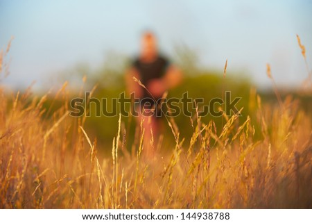 Young man is running on summer meadow - selective focus on grass - stock photo