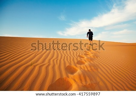 Young man is running to the top of dune in desert