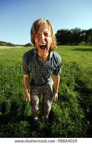 young man is screaming outdoors in summer - stock photo