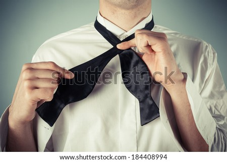 Young man is showing how to tie a formal bow tie - stock photo