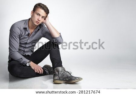 Young man is sitting on the floor on a white background - stock photo