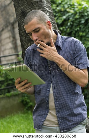 Young man is standing outside, searching the net on his tablet while smoking cigarette - stock photo
