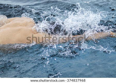 Young man is swimming the front crawl in a pool - stock photo