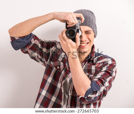 Young man is taking a picture with an old camera.
