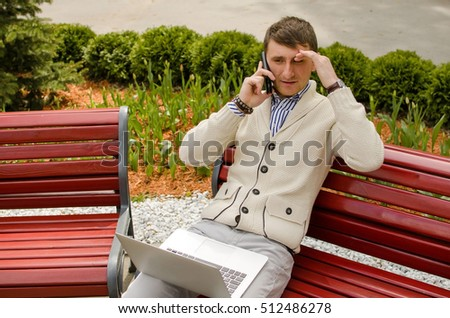 Young man is talking on the phone with laptop on his knees