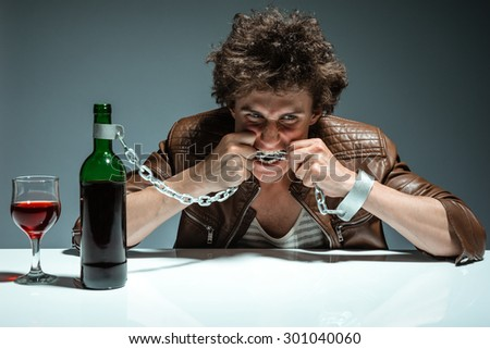 Young man is trying to gnaw the chains / photo of youth addicted to alcohol, alcoholism concept, social problem - stock photo