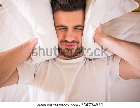 Young man is trying to sleep with a pillow over his head. - stock photo