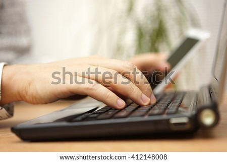 Young man is using laptop computer and mobile phone at the same time - stock photo