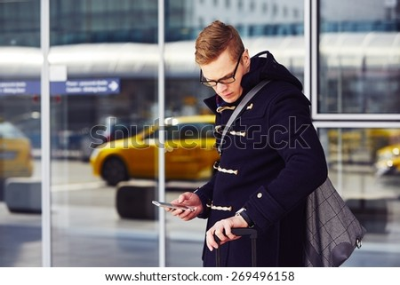 Young man is waiting for taxi at the airport. - stock photo