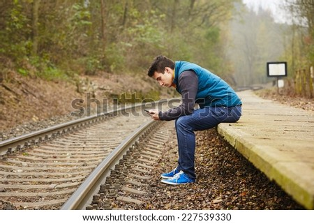 Young man is waiting on the platform rural railway station  - stock photo