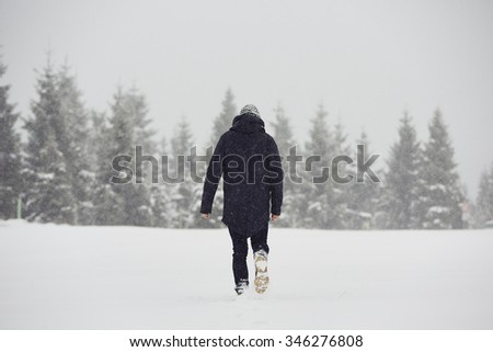Young man is walking in winter landscape - stock photo