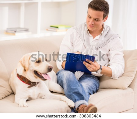 Young man is writing while sitting on sofa with his dog. - stock photo