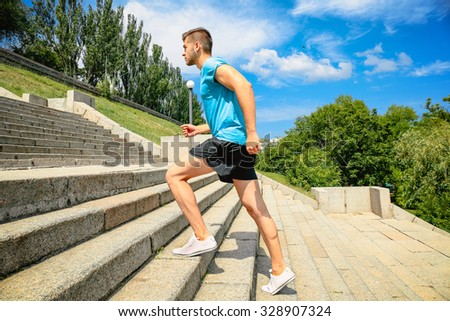 Young man jogging at stairs outdoors - stock photo