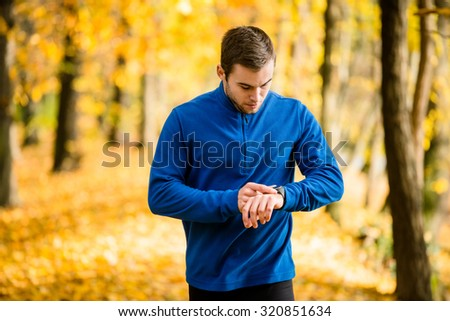 Young man jogging in beautiful fall nature and checking pulse on watches - stock photo