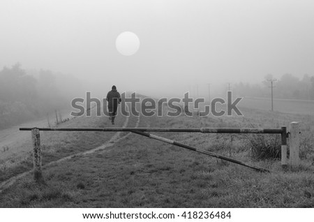 Young man jogging in nature on cold misty autumn day in black and white. - stock photo