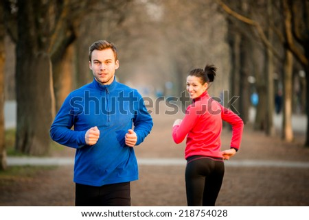 Young man jogging in park, woman running from opposite direction turns on him - stock photo