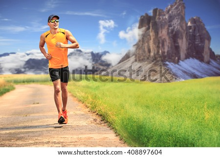 young man jogging through the fields - stock photo