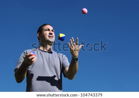 Young man juggler is juggling balls.concept photo of flexibility, success, skill and control.