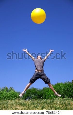 Young man jump in park with yellow ball