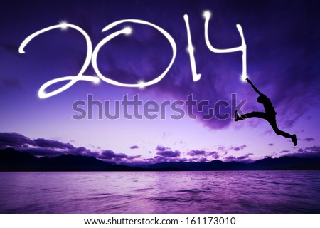 Young man jumping and drawing 2014 on the beach - stock photo