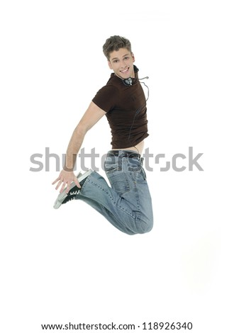 Young man jumping and listening music isolated