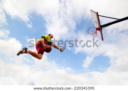 Young man jumping and making a fantastic slam dunk playing streetball, basketball. Urban authentic.   - stock photo