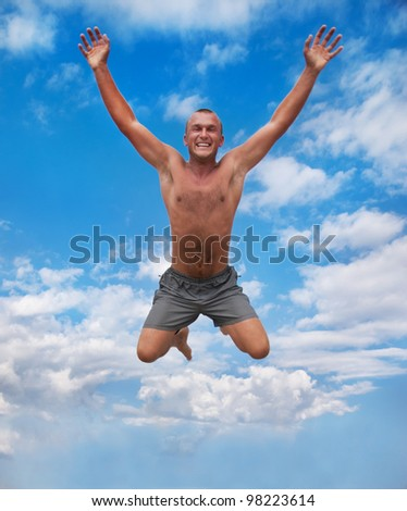 young man jumping and raising hands in the air against a blue sky - stock photo