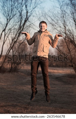 Young man jumping for joy outdoor  - stock photo