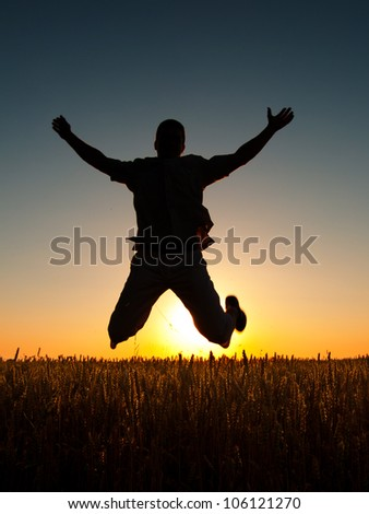 Young man jumping high in the air on sunny summer day. - stock photo