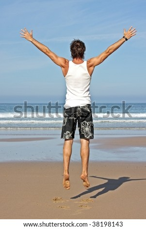 Young man jumping in the air out of joy at the atlantic ocean - stock photo