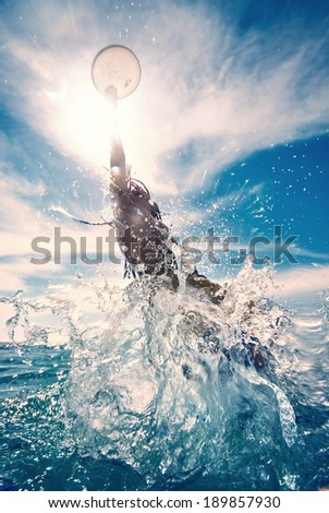 young man jumping in the water, summer beach activity, frisbee - stock photo
