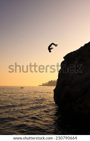Young man jumping into the water from cliff - stock photo