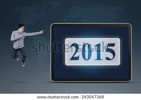Young man jumping near a board while pointing at number 2015 with world map background - stock photo