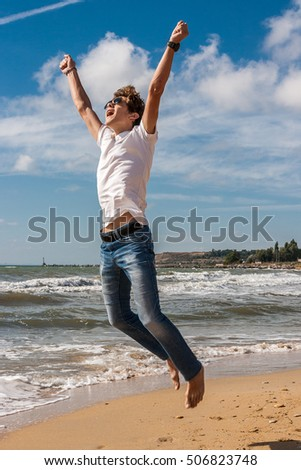 Young man jumping on the beach in the oncoming waves.