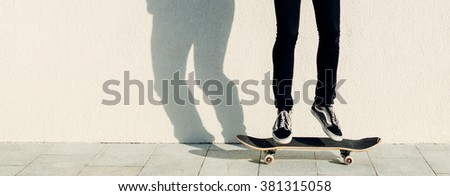 Young man jumping on the skateboard on city street - stock photo